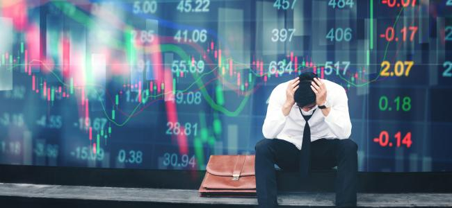 An image of a man with his head dropped sitting in front of a stock exchange board is shown.