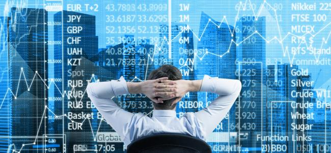 An image of a male with his hands folded behind his head sitting in front of a stock exchange board is shown.