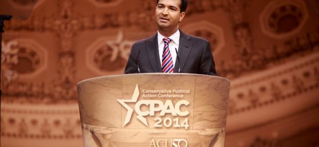An image of Representative Carlos Curbelo standing behind a podium is shown.