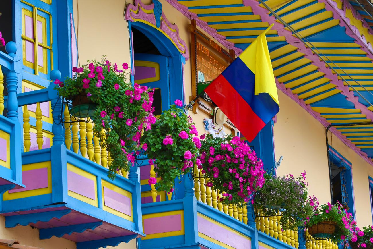 An image of the Colombian flag waving from a building with flower-lined balconies is shown.